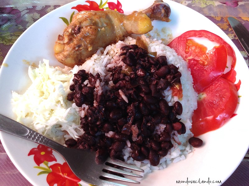 A typical Cuban meal with rice, beans, chicken, and cabbage.